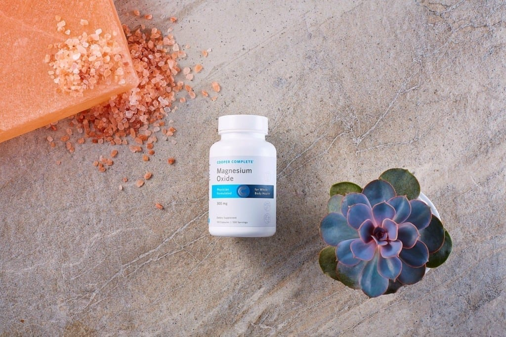 Cooper Complete Magnesium Oxide dietary supplement bottle and succulent plant and magnesium salts on a natural surface