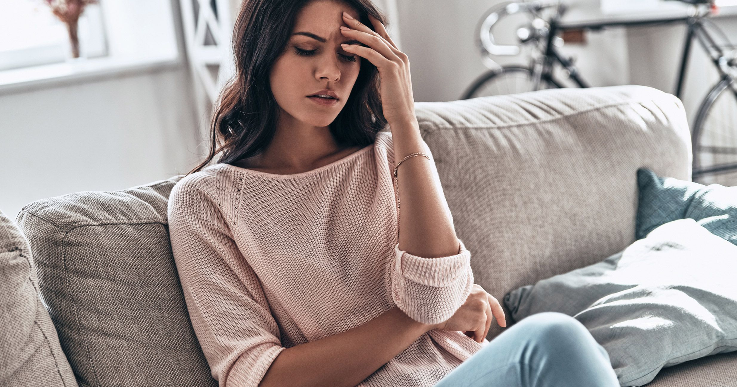 Migraine pains being felt by woman on a couch. Learn about vitamins and supplements for migraine relief