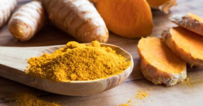 Turmeric powder and root on a wooden table, learn about turmeric supplement benefits