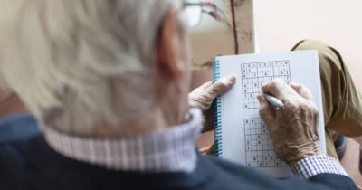 Photo looking over the shoulder of an older man playing Sudoku Keep learning for Alzheimer's Disease Prevention